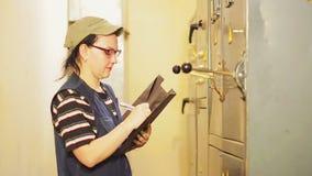 Un ingeniero eléctrico de sexo femenino registra las lecturas de aparatos eléctricos en la centralita telefónica almacen de metraje de vídeo