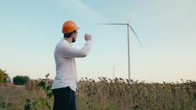 Un ingeniero en un casco protector anaranjado y gafas mira un generador de viento de la energía eléctrica en un campo verde despu almacen de video