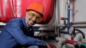 Un ingeniero en los trabajos en el cuarto de caldera, controles de los vidrios el mantenimiento del equipo del sistema de calefac metrajes