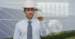 Un ingeniero-experto futurista en los paneles fotovoltaicos solares, aplicaciones un holograma con teledirigido, realiza acciones Imagen de archivo libre de regalías