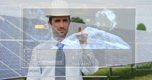 Un ingeniero-experto futurista en los paneles fotovoltaicos solares, aplicaciones un holograma con teledirigido, realiza acciones Imágenes de archivo libres de regalías