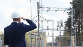 Un ingeniero joven, inspector, examina controles una central eléctrica almacen de metraje de vídeo