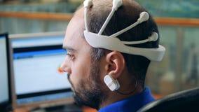 Un ingeniero que lleva los sensores de exploración especiales de la onda cerebral en una cabeza, visión trasera almacen de metraje de vídeo