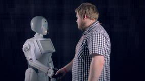 Un ingeniero saluda un robot blanco con un apretón de manos
