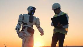 Un ingeniero y un droid en un fondo de la puesta del sol, cierre para arriba