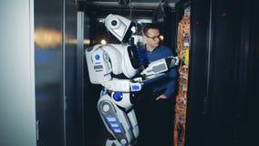 Un ingeniero y un soporte del cyborg en un cuarto especial, comprobando el equipo del servidor 4K