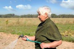 Un'innaffiatura anziana della donna Immagine Stock Libera da Diritti