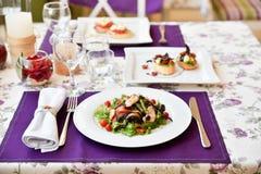 Un'insalata nel ristorante di primavera con i tovaglioli viola Immagini Stock