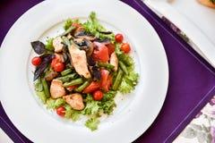 Un'insalata nel ristorante di primavera con i tovaglioli viola Immagine Stock