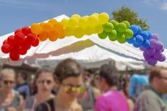 Un'insegna del pallone dell'arcobaleno sopra una tenda a Pride Festival immagini stock