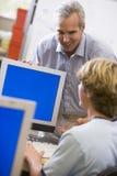 Un insegnante comunica con scolaro che per mezzo di un calcolatore Fotografie Stock Libere da Diritti