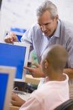 Un insegnante comunica con scolaro che per mezzo di un calcolatore Fotografia Stock