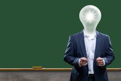 Un insegnante o un professore con una lampadina per una testa che sta davanti ad un bordo di gesso. Immagine Stock