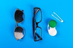 Un insieme degli accessori per vista Vetri di foro di spillo, lenti con il contenitore e vetri per vista Paia dei vetri medici di Fotografie Stock