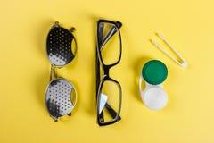 Un insieme degli accessori per vista Vetri di foro di spillo, lenti con il contenitore e vetri per vista Paia dei vetri medici di Immagine Stock