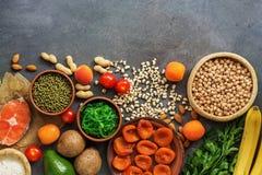 Un insieme degli alimenti alti in potassio in una fila su un fondo scuro Pasto equilibrato sano Vista superiore, disposizione pia fotografie stock