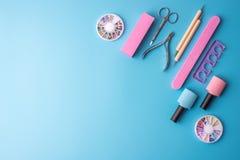 Un insieme degli strumenti cosmetici per il manicure ed il pedicure su un fondo blu Lucidi del gel, archivi di unghia e tagliator Immagine Stock Libera da Diritti