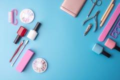 Un insieme degli strumenti cosmetici per il manicure ed il pedicure su un fondo blu Lucidi del gel, archivi di unghia e tagliator Immagine Stock