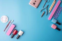 Un insieme degli strumenti cosmetici per il manicure ed il pedicure su un fondo blu Lucidi del gel, archivi di unghia e tagliator Fotografie Stock