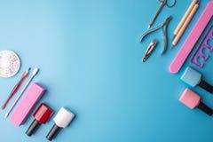 Un insieme degli strumenti cosmetici per il manicure ed il pedicure su un fondo blu Lucidi del gel, archivi di unghia e tagliator Fotografia Stock Libera da Diritti