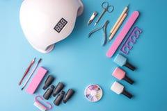 Un insieme degli strumenti cosmetici per il manicure ed il pedicure su un fondo blu Lucidi del gel, archivi di unghia e tagliator Fotografia Stock