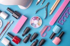 Un insieme degli strumenti cosmetici per il manicure ed il pedicure su un fondo blu Lucidi del gel, archivi di unghia e tagliator Immagini Stock Libere da Diritti