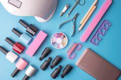 Un insieme degli strumenti cosmetici per il manicure ed il pedicure su un fondo blu Lucidi del gel, archivi di unghia e tagliator Fotografie Stock Libere da Diritti