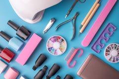 Un insieme degli strumenti cosmetici per il manicure ed il pedicure su un fondo blu Lucidi del gel, archivi di unghia e tagliator Immagini Stock