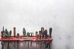 Un insieme degli strumenti funzionanti della costruzione su una parete intonacata bianca immagini stock