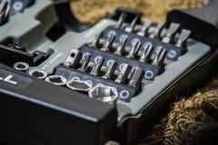 Un insieme degli ugelli per un cacciavite nella scatola grigia sul panno ruvido Fotografia Stock Libera da Diritti