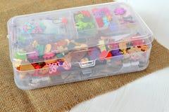 Un insieme dei bottoni differenti nell'organizzatore sulla tela da imballaggio Fotografia Stock