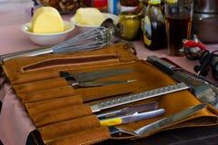 Un insieme dei coltelli e del fornello professionale del cuoco unico della spatola contro Th Fotografia Stock