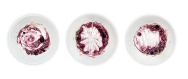 Un insieme dei piatti bianchi con porridge ed il mirtillo inceppano le rimanenze isolate su fondo bianco Concetto estetico di Mes Immagini Stock