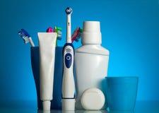 Un insieme dei prodotti orali di cura e di vari spazzolini da denti sullo scaffale Fotografie Stock