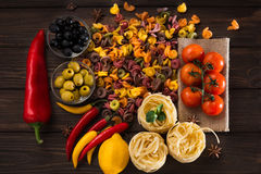 Un insieme dei prodotti per pasta Il menu italiano Peperoni rossi e gialli rossi dei peperoni dolci, pomodori, pasta, olive e Immagini Stock