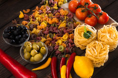 Un insieme dei prodotti per pasta Il menu italiano Peperoni rossi e gialli rossi dei peperoni dolci, pomodori, pasta, olive e Fotografia Stock Libera da Diritti