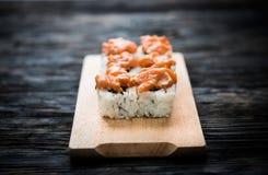 Un insieme dei rotoli di sushi con guarnizione di color salmone sul bordo di legno Fotografie Stock