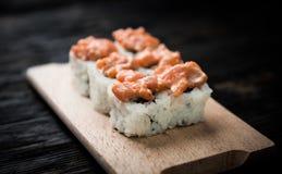 Un insieme dei rotoli di sushi con guarnizione di color salmone sul bordo di legno Fotografie Stock Libere da Diritti