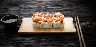 Un insieme dei rotoli di sushi con guarnizione di color salmone sul bordo di legno Immagine Stock Libera da Diritti