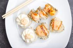 Un insieme dei rotoli di sushi e dei bastoncini giapponesi tagliati su un primo piano bianco del piatto fotografie stock libere da diritti