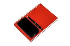Un insieme del blocco note, del telefono cellulare e della penna. Immagini Stock Libere da Diritti