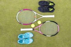 Un insieme dell'attrezzatura di tennis di due racchette di tennis, due palle, maschio e Fotografia Stock