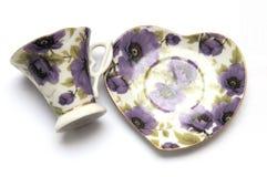 Un insieme della tazza e del piattino di tè con la flora porpora stampa Fotografia Stock