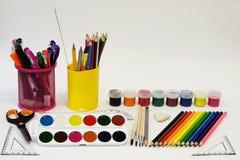 Un insieme delle matite colorate e un insieme delle pitture colorate Fotografia Stock Libera da Diritti
