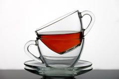 Un insieme delle tazze di tè ha versato il tè nero Immagini Stock Libere da Diritti