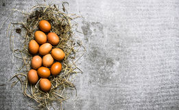 Un insieme delle uova nel fieno Su fondo di pietra Immagini Stock