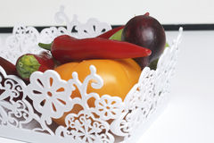 Un insieme delle verdure per insalata si trova in un canestro del pizzo Su una priorità bassa bianca Cipolle e pomodori dei color Fotografie Stock