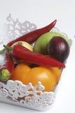 Un insieme delle verdure per insalata si trova in un canestro del pizzo Su una priorità bassa bianca Cipolle e pomodori dei color Fotografia Stock