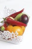 Un insieme delle verdure per insalata si trova in un canestro del pizzo Su una priorità bassa bianca Cipolle e pomodori dei color Immagini Stock Libere da Diritti