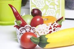 Un insieme delle verdure per insalata si trova in un canestro del pizzo Su una priorità bassa bianca Cipolle e pomodori dei color Immagine Stock